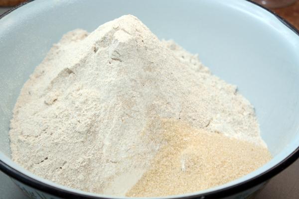 Как обычно, начинаем с просеивания муки в большую миску.  В муку добавляем дрожжи, соль и сахар, затем наливаем 650 мл тепловатой воды.  Хочу отметить, что коричневый сахар в этом рецепте использовать предпочтительнее, хотя и не обязательно.