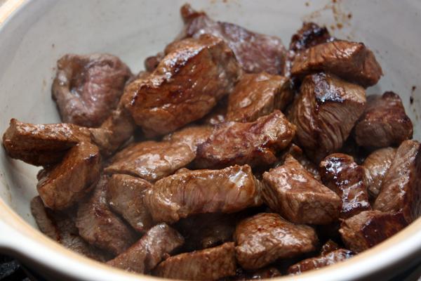 Обжаренное мясо выложить в кастрюлю или глубокую сковороду с толстыми стенками, немного посолить.