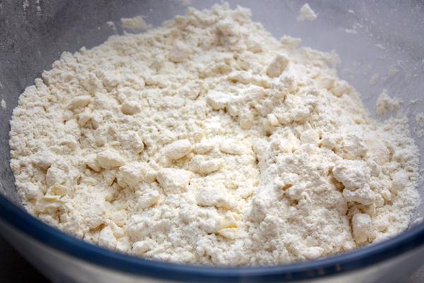 Добавить просеянную муку и сахар, порубить до состояния крошки.