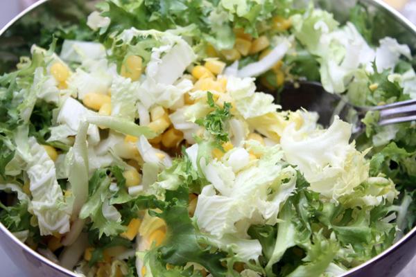 В миске смешиваем нарезанные или разорванные руками листочки салатов и банку молодой кукурузы.