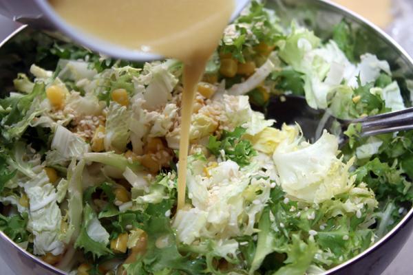 Добавляем в салат кунжут, заправку и перемешиваем. Кунжутом также можно посыпать готовое блюдо.