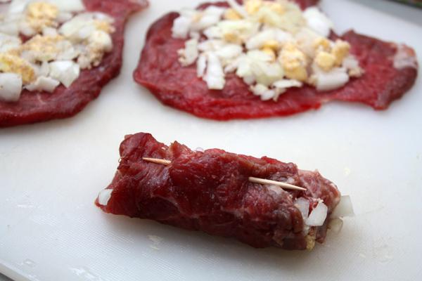 На каждый кусочек мяса выложить начинку, распределив ее равномерно, и свернуть рулетиком. Края закрепить зубочисткой.
