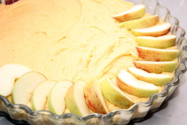 В смазанную сливочным маслом форму выкладываем тесто и слегка разравниваем.   Сверху по кругу укладываем дольки яблок слегка внахлест.