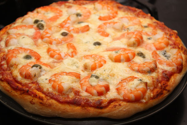 Печь пиццу нужно в очень горячей духовке (220-250 градусов) на среднем уровне около 10 минут.  Точные цифры зависят от вашей духовки, так что следите внимательно!