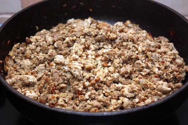 Обжарить лук в растительном масле до прозрачности и добавить мясной фарш. Продолжать жарить все вместе, часто помешивая, пока не испарится большая часть мясного сока.  Фарш должен в итоге обжариться и не слипнуться в большие комки.