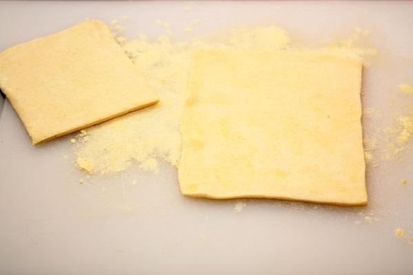Слоеное тесто нужно предварительно разморозить. От теста отрезать квадратики примерно 10х10 см (зависит от толщины исходного куска, конечно) и раскатывать их на посыпанной мукой поверхности толщиной около 0.5 см в виде прямоугольников.