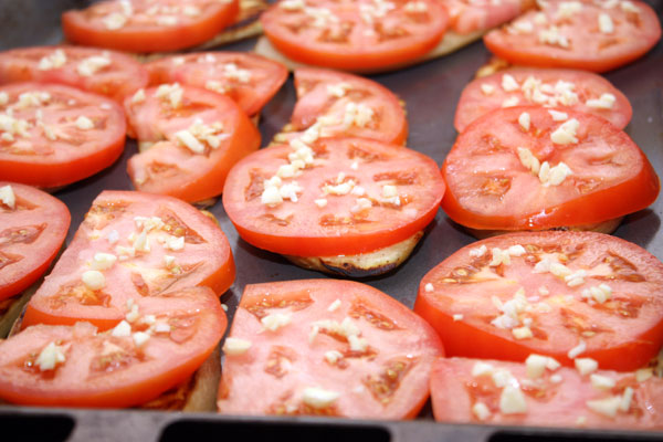 Поверх баклажанов положить кружочки помидоров и посыпать мелко нарезанным чесноком.