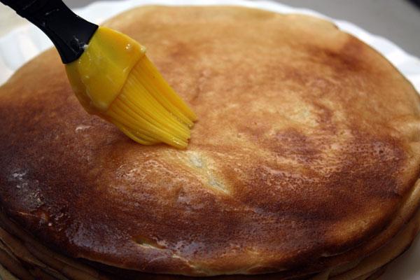 Готовые блины складываем в стопку и, при помощи кулинарной кисточки, хорошо смазываем каждый блин сливочным маслом.  Когда тесто закончится, блины можно подавать к столу.