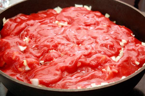 В сковороду с курицей добавить нарезанный лук, томатное пюре (приготовить самостоятельно или использовать готовое, главное — не путать пюре с томатной пастой), вино (Мадера, портвейн), соль и перец.  Если соус получается густым, добавьте немного мясного бульона. Мне этого не потребовалось.