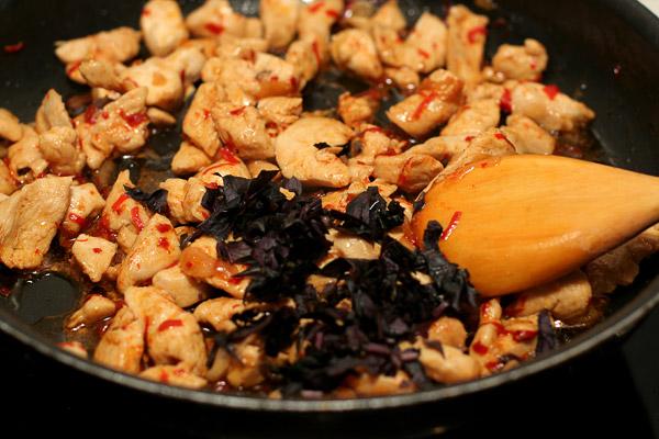 Помыть, высушить и нарезать базилик, добавить в курицу.    Выложить на подогретое блюдо.   А если дополнить это блюдо украшением из листьев базилика, обжаренных во фритюре, то вы откроете для себя новое вкусовое измерение.