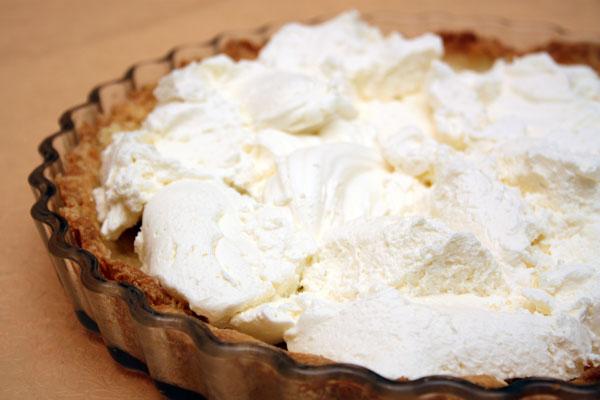На остывший корж кладем сливки и распределяем их равномерным слоем. Если крем мягкий, ставим пирог в холодильник, чтобы он слегка застыл.