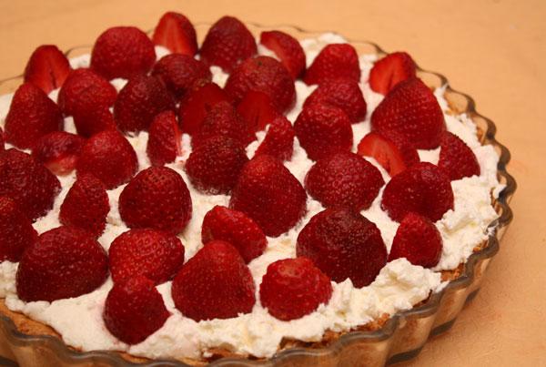 Вымытую клубнику раскладываем на сливочном слое довольно плотно. Можно оставить ягоды целыми или разрезать на 2-4 части.
