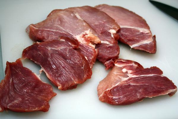 Свиную шейку нарежем ломтиками поперек волокон толщиной около 1,5 см. Можно мясо немного отбить, если вы не уверены в его мягкости, хотя если вы используете свежую свиную шейку, то это не обязательно.