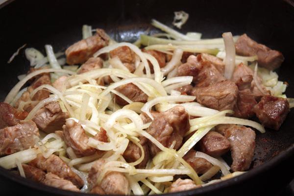 Тонко порезанный полукольцами лук добавить к обжаренному мясу и продолжать готовить на среднем огне.
