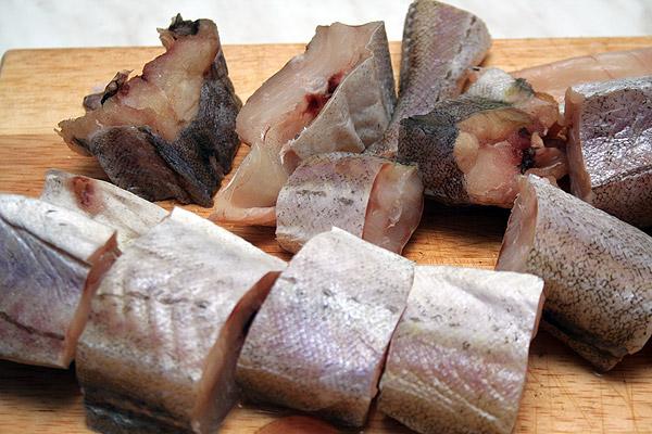 Обрезать плавники на рыбе и порезать ее на кусочки.