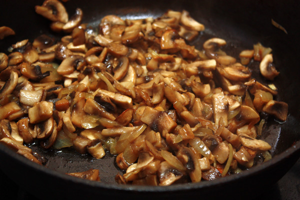 Сначала нужно немного обжарить тонко нарезанный лук, а затем добавить туда кусочки шампиньонов. Думаю, их можно заменить вешенками или лесными грибами.