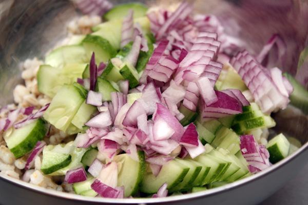 Одновременно с перловкой ставим варить кусочек постной говядины.<br>Пока все это варится, режем огурец и красный сладкий лук небольшими кусочками. Добавляем в салат.