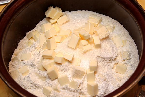 Муку с разрыхлителем и щепоткой соли просеиваем и добавляем сахар. Закидываем нарезанное маленькими кубиками сливочное масло.