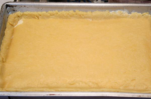 Раскатываем тесто в два тонких пласта. Один выкладываем на понравившуюся форму, организуем бортики и вываливаем туда начинку. Второй пласт можно нарезать ленточками и выложить сверху сеточкой или как я полностью накрыть.<p>Смазываем поверхность последним яйцом и в духовку!