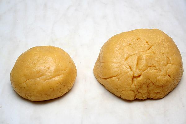 Муку просеять и смешать с разрыхлителем. Постепенно в муку ввести яично-масляную смесь, непрерывно перемешивая. Замесить тесто. Отделить треть теста, завернуть в пищевую пленку и отправить на 30-40 минут в морозильную камеру.