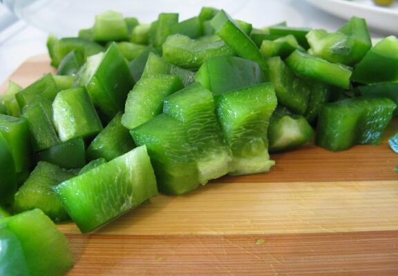 Режем зелёный перец небольшими кусочками, не больше, чем получились наши огурцы. Кстати, как оказалось, зелёный перец встречается в продаже не так часто, и, возможно, у вас будет соблазн заменить его, например, красным. Не делайте этого! :) Во-первых, красный перец придаст салату излишне сладкие нотки, а, во-вторых, он нарушит зелёную гамму всего этого блюда, придав ему совсем другой эмоциональный окрас. При отсутствии зелёного перца лучше просто сделать салат без него - получается тоже вполне неплохо!