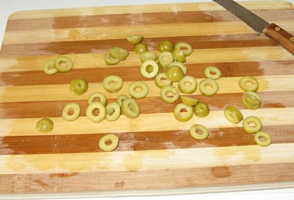 Несколько консервированных оливок без косточки режем поперёк колечками на 3-4 части каждую.