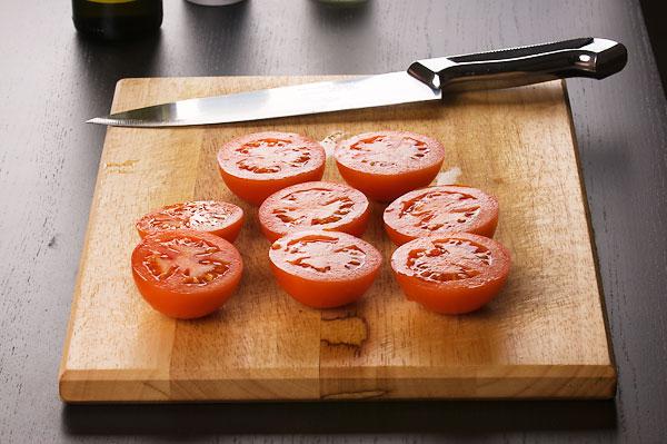 Помидоры разрезать вдоль пополам, приправить солью и перцем.