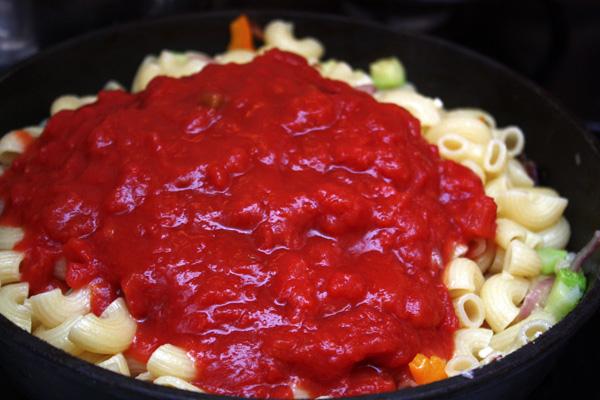 Добавляем в овощи пасту и очищенные измельченные томаты. Все вместе доводим до кипения и сразу же подаем.
