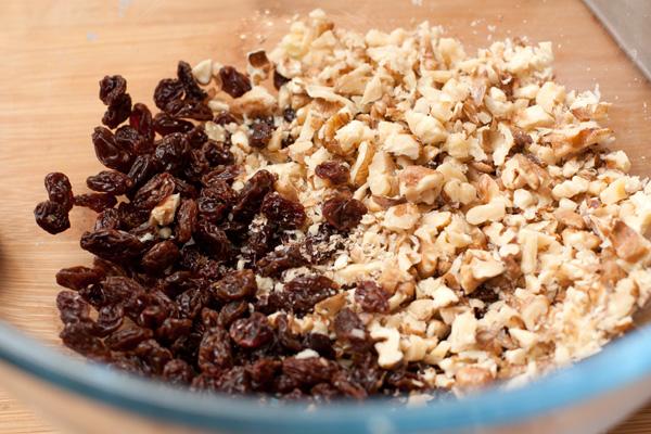 Изюм моем, просушиваем и соединяем с нарезанными грецкими орехами. Кладем в большую миску для начинки.