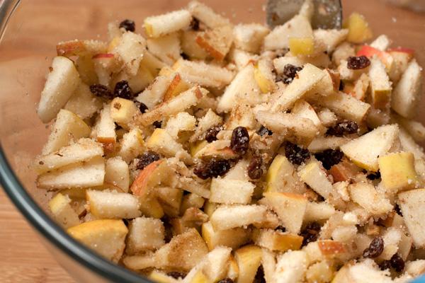 Вымытые и обсушенные яблоки очистите от сердцевины и некрупно нарежьте. Сбрызните лимонным соком.  Положите яблоки в миску к изюму и орехам, добавьте сахар, и корицу.