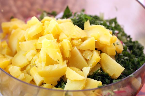 Картофель нарежьте мелкими кубиками, как огурцы. Зелень измельчите, предварительно отрезав у петрушки и укропа жесткие стебли.