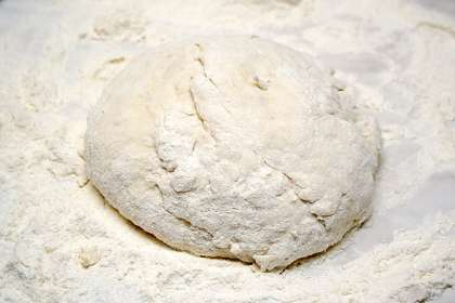 В муку добавить соль и перемешать. Залить в муку 150 мл теплой воды и замесить тесто.