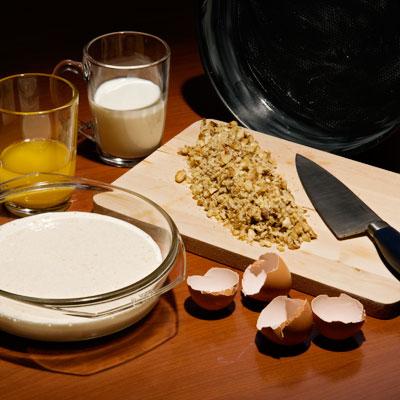 Измельчите орехи и смешайте с мукой. Добавьте разрыхлитель теста. Полученную смесь попеременно с молоком добавляйте в яично-масляную пену. Смажьте сливочным маслом форму для выпечки.