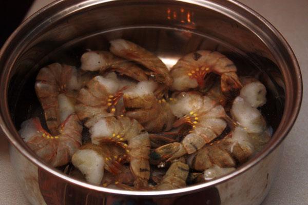 Креветки доводим до кипения и варим 1 минуту на среднем огне. Готовые креветки нужно очистить.  В этом салате лучше использовать королевские креветки, однако обычные тоже подойдут, но тогда лучше покупать сразу очищенные.