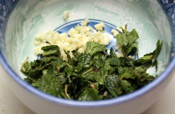 Готовим заправку — для этого смешиваем мелко нарезанный чеснок, мяту, щепотку соли, оливковое масло и лимонный сок.  Все ингредиенты тщательно перетираем.