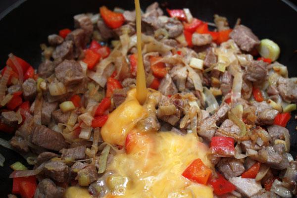 Овощи и мясо быстро обжариваем на большом огне, постоянно помешивая.  Это должно занять около 5-7 минут. Когда мясо поджарится, а овощи станут мягкими, нужно добавить в сковороду взбитые яйца, продолжая интенсивно мешать.  Солить не надо, так как в соевом соусе содержится достаточное количество соли.