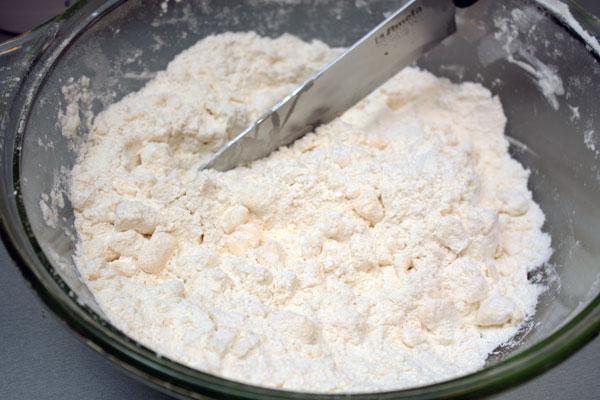 Для нижнего слоя пирога надо сделать несладкое рубленое тесто. Смешиваем холодное сливочное масло, муку и соль. Режем ножом эту смесь до образования крошек.