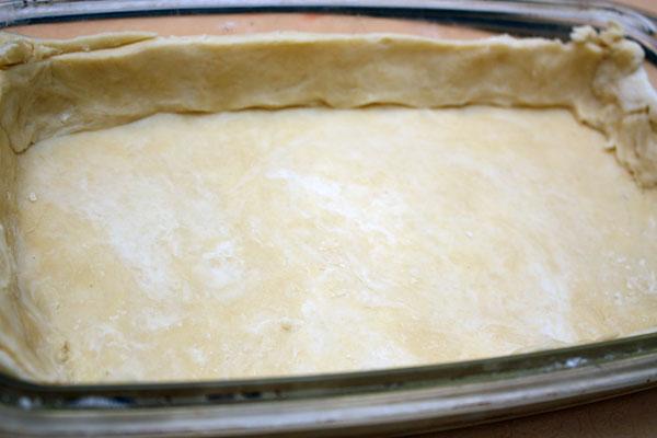 Достаем наше тесто, раскатываем его толщиной около 0,5 см и выкладываем им невысокую форму для выпечки, делая бортики из теста.