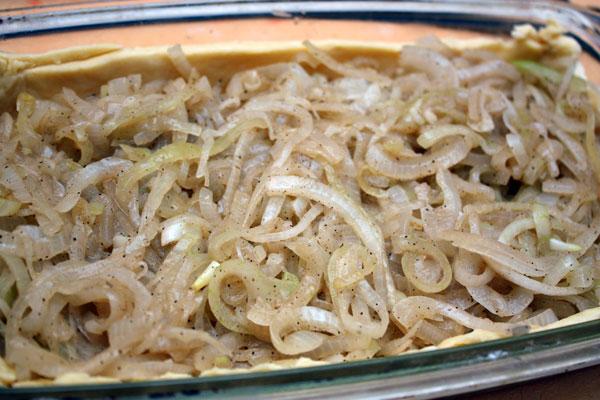 На тесто выкладываем остывший лук и заливаем его взбитой с яйцами сметаной.