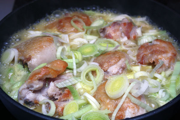 В сковороду с курицей добавить 200 мл апельсинового сока, коньяк и порей. Посолить, поперчить.<br>Накрыть крышкой и тушить на небольшом огне в течение 15 минут, пока курица не станет мягкой и полностью приготовленной.