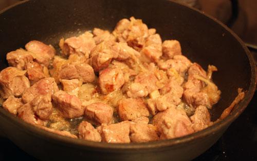 Обжариваем нарезанный соломкой репчатый лук в растительном масле и добавляем туда свинину. Жарим мясо до полуготовности.