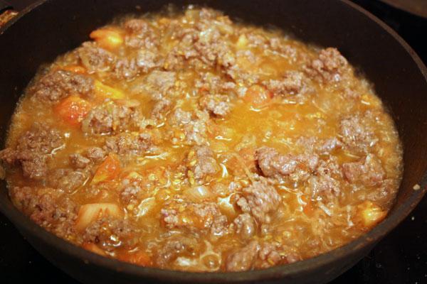 Лук мелко режем и обжариваем на растительном масле до прозрачности. Туда же кладем мясной фарш, обжариваем его до готовности и добавляем извлеченную из помидоров мякоть.