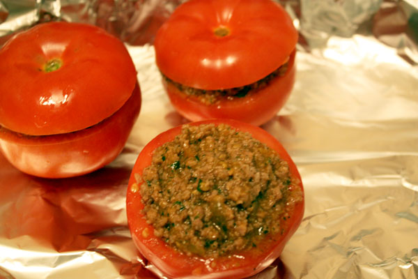 Форму для запекания выложить фольгой. На нее положить подготовленные помидоры, наполненные фаршем и закрытые срезанной верхней частью. Сбрызнуть помидоры оливковым маслом.<p>  Запекать их в разогретой до 200 градусов духовке минут 15, до мягкости помидоров.