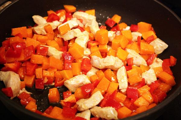 На сильно разогретой сковороде с оливковым маслом обжариваем кусочки индейки, тыкву и сладкий перец.  В первую очередь кладем индейку, затем овощи и грибы. Всего это должно занять около 10-15 минут.