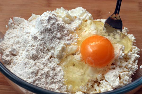 Смешайте творог с творожной массой и яйцом. Добавьте ванильный сахар или ванильный экстракт и три полные столовые ложки муки, хорошо размешайте.