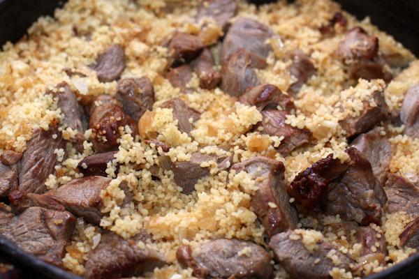 Плотно накройте крышкой и дайте постоять 5-7 минут, чтобы кускус впитал воду и пропитался мясным ароматом.