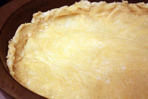 Охлажденное тесто раскатываем и распределяем руками по широкой плоской форме для выпечки, накалываем вилкой, насыпаем сухой фасоли и ставим в разогретую до 190 градусов духовку минут на 15.