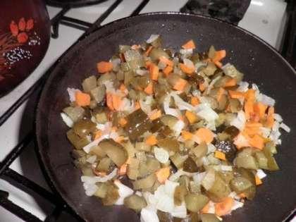 Смешать лук, морковь, соленые огурцы и обжарить на масле в течение 10 минут