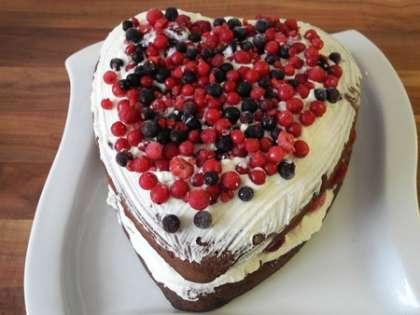 Сверху на сливки выложить ягоды. В такой же последовательности выложить оставшиеся коржи, смазав их сливками и выложив сверху ягодами.Обмазать края торта сливками
