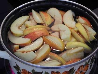 В кастрюлю налить воду, добавить яблоки и бруснику